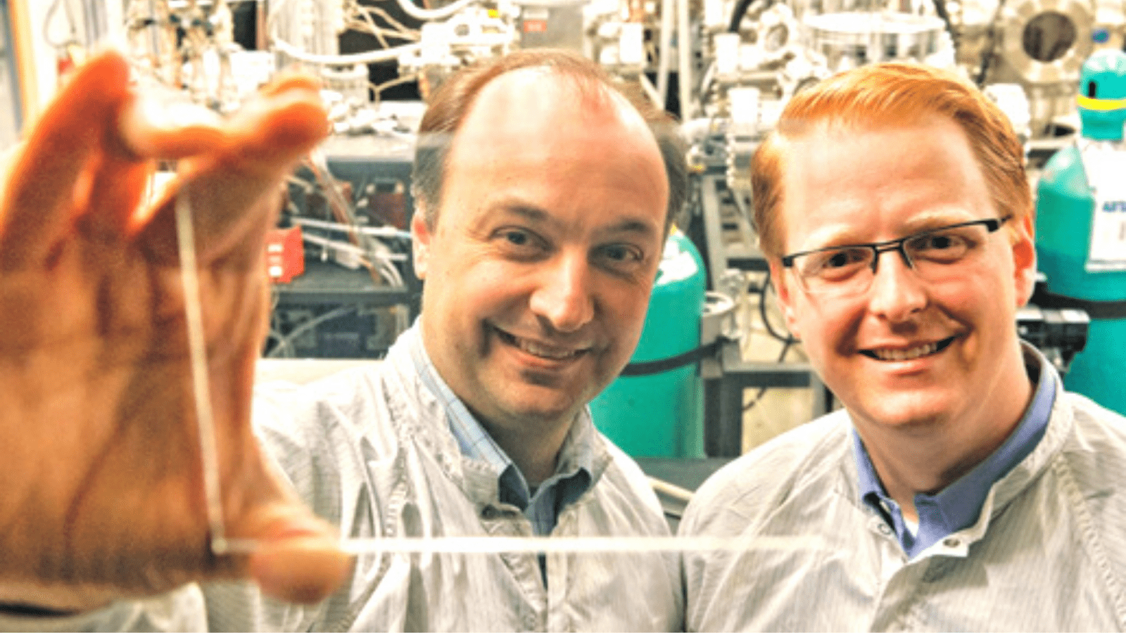 Researchers at MIT holding Transparent Solar Cell